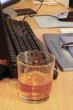 Drink at work. Whiskey glass on office desk depicting drinking at work Royalty Free Stock Photography