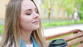 Drinkar och folkbegrepp - lycklig ung kvinna eller tonårs- flicka som dricker kaffe från den pappers- koppen som sitter på på sta lager videofilmer