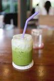 Drinken för grönt te av förkylning mjölkar på tabellen Arkivbild