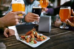Drinkend Bier Vrienden die Glazen Bier opheffen Royalty-vrije Stock Afbeeldingen