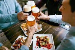 Drinkend Bier Vrienden die Glazen Bier opheffen Royalty-vrije Stock Foto