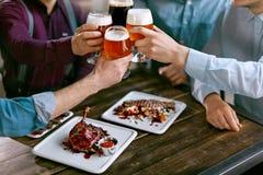 Drinkend Bier Vrienden die Glazen Bier opheffen Stock Foto's