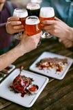 Drinkend Bier Vrienden die Glazen Bier opheffen Stock Afbeeldingen