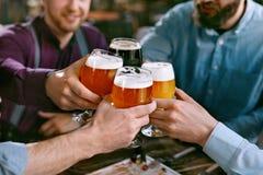 Drinkend Bier Vrienden die Glazen Bier opheffen Stock Afbeelding