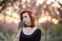 Drinkend koffie van document mokkop - de Gelukkige jonge vrouw die van de reisdanser van vrije tijd in een de bloesempark van de  stock fotografie