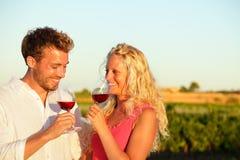 Drinkend rode wijnpaar bij wijngaard Royalty-vrije Stock Afbeeldingen