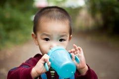 Drinkende Aziatische jongen stock foto's