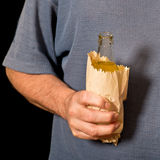 Drinker holds a bottle in the paper bag. Shallow depth of field Royalty Free Stock Photos