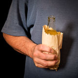 Drinker holds a bottle in the paper bag. Shallow depth of field Stock Images