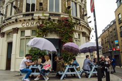 Drinkers at the Commercial Tavern, Shoreditch. LONDON, UNITED KINGDOM - AUGUST 30, 2014:  Drinkers enjoying the open air tables outside the fashionable Royalty Free Stock Photos
