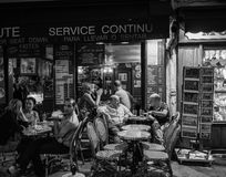 Drinkers at an outdoor Paris cafe in the evening; Montmartre, late summer evening. Black and white photo of drinkers in conversation at a cafe on Montmartre in Royalty Free Stock Photos