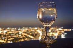 Drinkexponeringsglas och stadshorisont Royaltyfri Bild