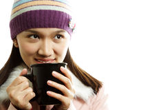 Drinking. A beautiful girl wearing winter dress holding a cup of hot drink Stock Photography