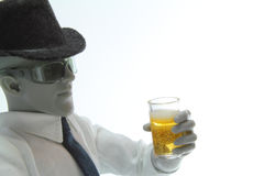 Drinking. Male figure dressed as a business man drinking a glass of beer Stock Images