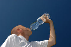 Drinking. Young man with a bottle of water Royalty Free Stock Photo