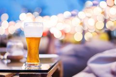 Drinking Alcohol  in Summer Night Party or Event Concept. Glass. Of Beer on Table. Blurred Light Bokeh as background Royalty Free Stock Photos