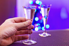 Drinking alone at Christmas. Hand taking glass of vodka at christmas time Stock Images