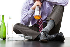 Drinking alone on the floor. Drunk businessman alcoholic sitting on the floor and finishing a bottle of cognac Royalty Free Stock Photography