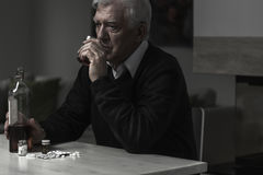 Drinking alone. Photo of older sad man drinking alcohol alone Royalty Free Stock Images