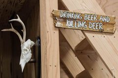 Drinking Beer and Killing Deer. A hunting lodge detail including a funny beer and deer sign and a mounted deer skull with antlers Royalty Free Stock Photography