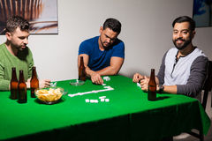 Drinking beer and playing dominoes. Three Hispanic friends having fun at night and playing some dominoes at home during poker night Royalty Free Stock Images
