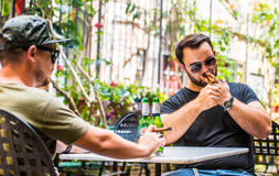Drinking beers and smoking a cigar. Two young guys having a beer in an outdoor bar and enjoying the nice weather, Having fun cracking some beers and making Stock Photos