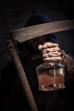 Drinking beverage is the shortest way to die. Dreadful death character is holding a scythe. He is stretching forward the bottle of alcohol drink with threats Stock Photos