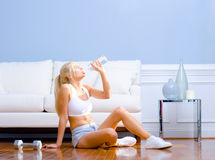 Drinking Bottled Water. Side view of a young woman drinking bottled water after exercising. Horizontal shot royalty free stock photos