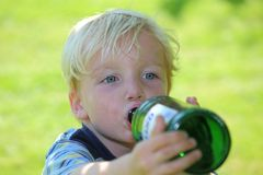 Drinking boy. Young boy drinks water out of a bottle Stock Images