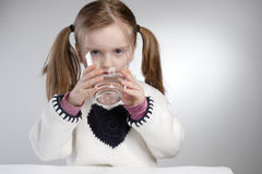 Drinking child. Little girl drinking glass of water Royalty Free Stock Photography