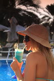 Drinking a cocktail by the pool stock image