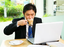 Drinking cofee while working in cafe. Situated inside the caf� that surrounded by glass wall, he is working with his laptop while drinking the coffee. Clean Royalty Free Stock Photo
