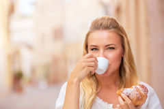 Drinking coffe outdoors. Portrait of beautiful blond woman sitting in outdoors cafe in Italy, drinking coffee and eating croissant, happy travel to Europe Royalty Free Stock Images
