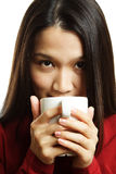 Drinking coffee. A beautiful young woman drinking a hot cup of coffee Stock Photography