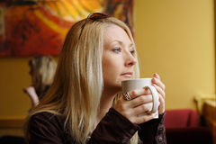 Drinking coffee. Young lady enjoying a mug of coffee in a coffee house royalty free stock image