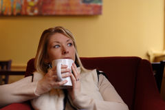 Drinking coffee. Young lady enjoying a mug of coffee in a coffee house stock photography