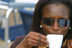 Drinking Coffee. A beautiful African American woman drinking coffee Stock Images