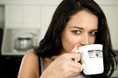 Drinking coffee. An atrractive female pours herself a cup of delicious coffee in the morning Stock Image