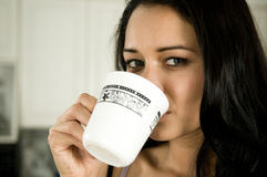 Drinking coffee. An atrractive female pours herself a cup of delicious coffee in the morning royalty free stock photo