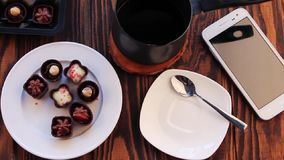 Drinking coffee with chocolate candies. On wooden table stock video