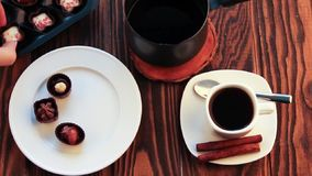 Drinking coffee with chocolate candies. On wooden table stock footage