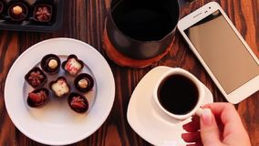 Drinking coffee with chocolate candies. On wooden table stock video footage