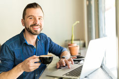 Drinking coffee and doing some work. Portrait of a good looking young Hispanic man using a laptop for work and drinking coffee in a restaurant Stock Photo