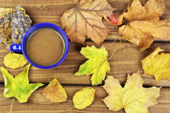 Drinking coffee in the fall on wooden table Royalty Free Stock Image