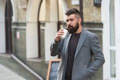 Drinking coffee on the go. Businessman lumbersexual appearance enjoy coffee break out of business center. Relax and. Recharge. Man bearded hipster drinking royalty free stock photography