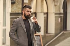 Drinking coffee on the go. Businessman lumbersexual appearance enjoy coffee break out of business center. Relax and royalty free stock photography