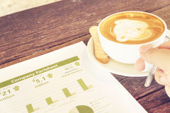 Drinking coffee latte reading company business factsheet statist Stock Photography