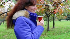 Drinking coffee outdoors. Woman walk in autumn park. stock video footage