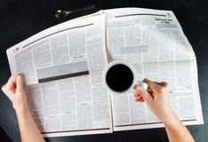 Drinking coffee and reading the newspaper. Over black table Royalty Free Stock Photos