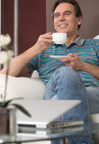 Drinking coffee at Sunday morning. Cheerful mature man sitting o Stock Photography
